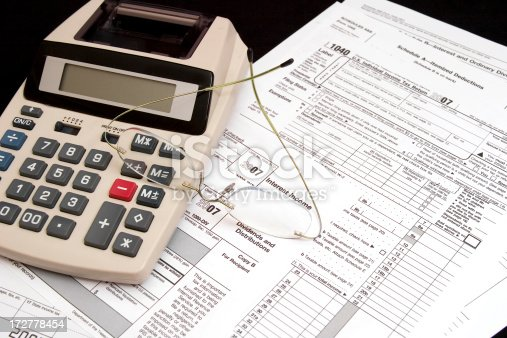 US Internal Revenue Service tax forms for individual income itemized deductions and interest and dividend income with calculator and eyeglasses.***check out my other Tax Form images***
