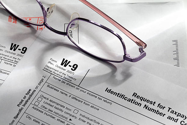 W-9 Tax Forms W-9 Tax forms with glasses and letters. annually stock pictures, royalty-free photos & images