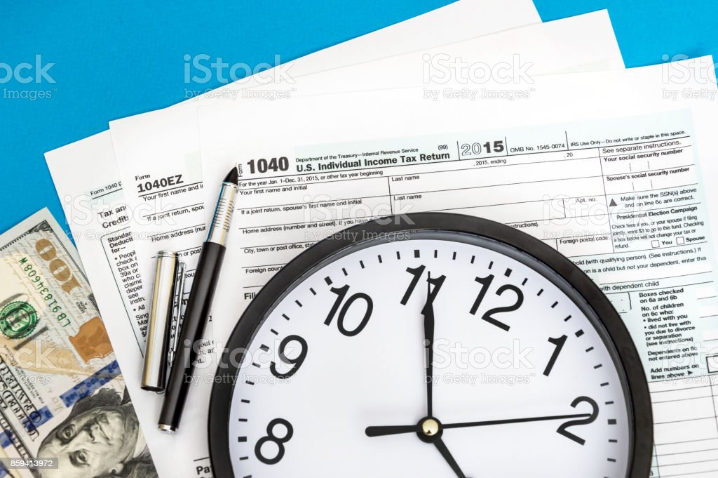 Tax forms with clock and money on blue background. Business concept. stock photo