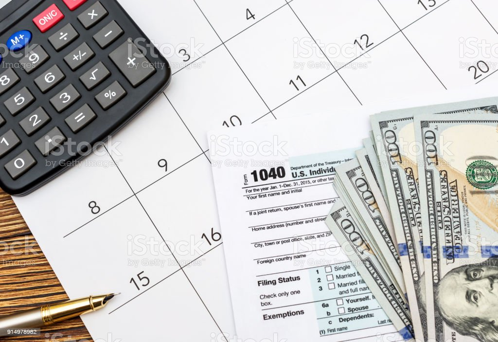 tax forms with money calculator and calendar on the table business