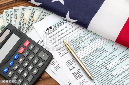 947260978 istock photo Tax forms with pen, calculator, money and american flag on the table. 924983150
