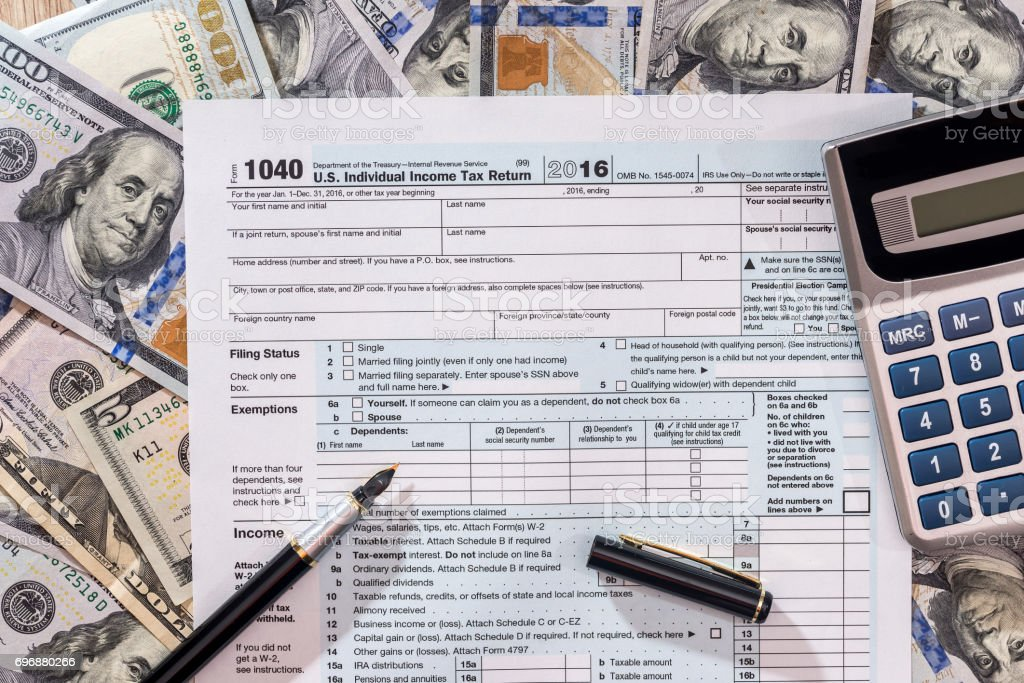 1040 tax from with us dollar banknote, pen and calculator. stock photo