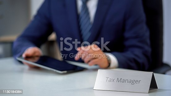 1130184417 istock photo Tax manager working on electronic tablet pc, viewing business files on screen 1130184384