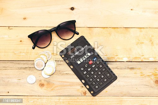tax on calculator concept. algeria coins and sunglasses