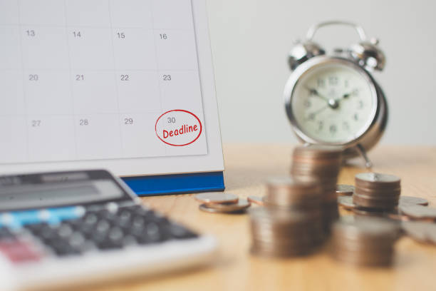 Tax payment season and finance debt collection deadline concept. Money coins stack, calendar, calculator and clock Tax payment season and finance debt collection deadline concept. Money coins stack, calendar, calculator and clock approaching stock pictures, royalty-free photos & images