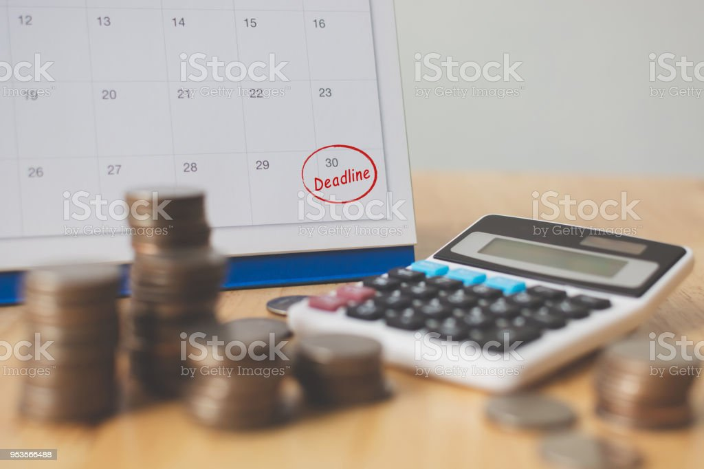 Tax payment season and finance debt collection deadline concept. Money coins stack, calendar and calculator stock photo
