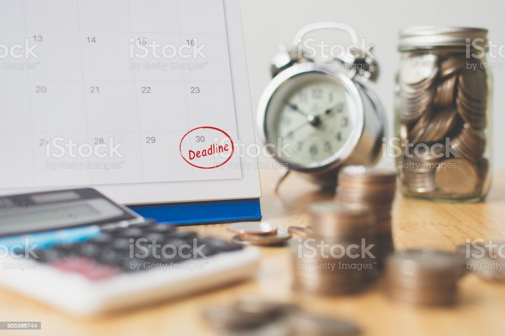 Tax payment season and finance debt collection deadline concept. Money coins stack, calendar, calculator and clock stock photo