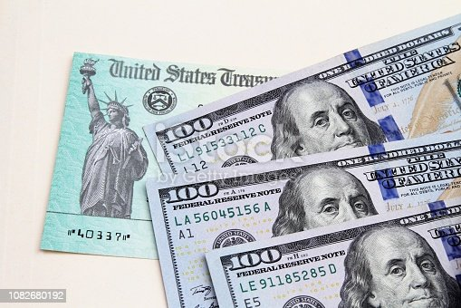 Tax refund check from US Treasury and US currency 100 dollar bills. Treasury check could be for tax refund, social security payment or other financial government benefits.