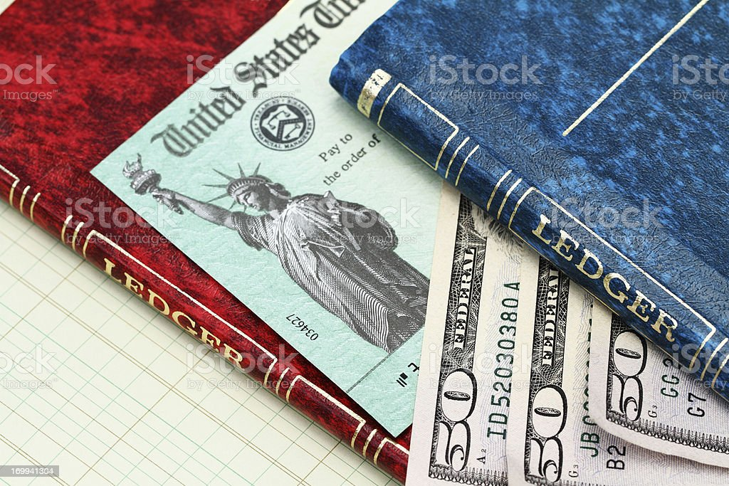 irs tax refund check with money and account ledgers stock photo