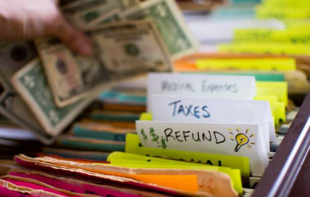 Tax refund ideas conceptual filing taxes photography with cash in hand stock photo