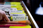 istock Tax refund ideas filing taxes woman's hand in filing cabinet 1190547795