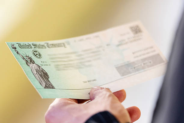 Tax refund Men hands holding a US Government Treasury check refund stock pictures, royalty-free photos & images