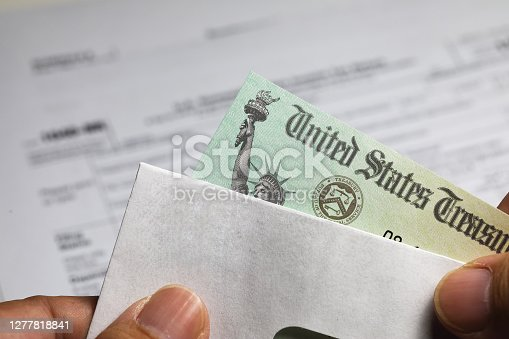 Man holding U.S. government Treasury tax refund check and envelope in his hand