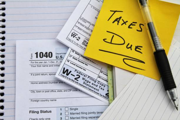 Tax return forms and wage statements with note Taxes Due. stock photo