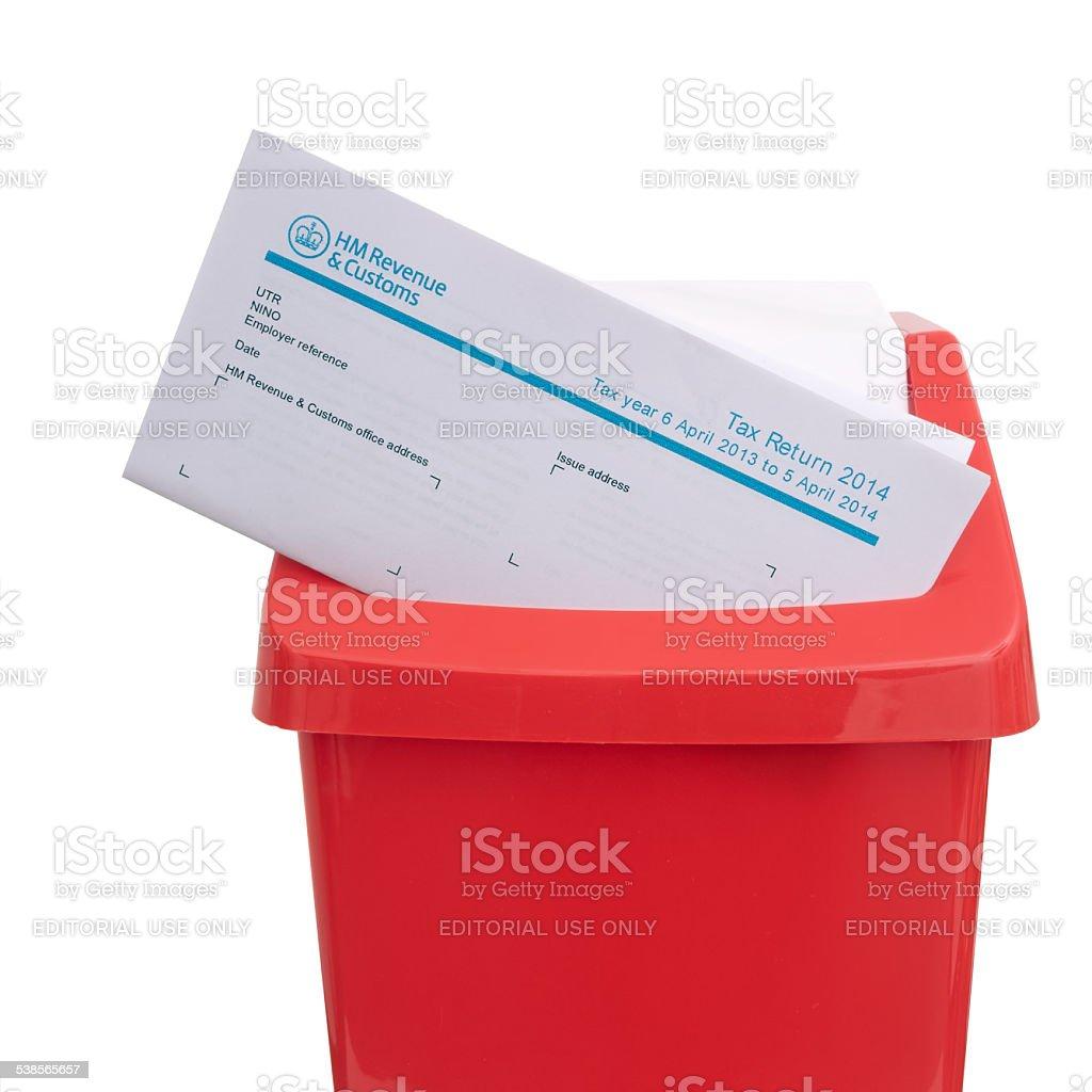 UK tax return in red plastic rubbish bin. Avoidance, evasion stock photo