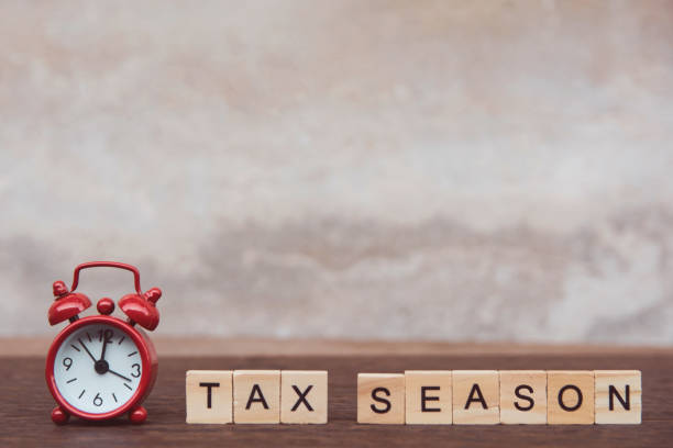 Tax season with wooden alphabet blocks and Red alarm clock, on Table dark plank wooden background with copy space Tax season with wooden alphabet blocks and Red alarm clock, on Table dark plank wooden background with copy space taxes stock pictures, royalty-free photos & images
