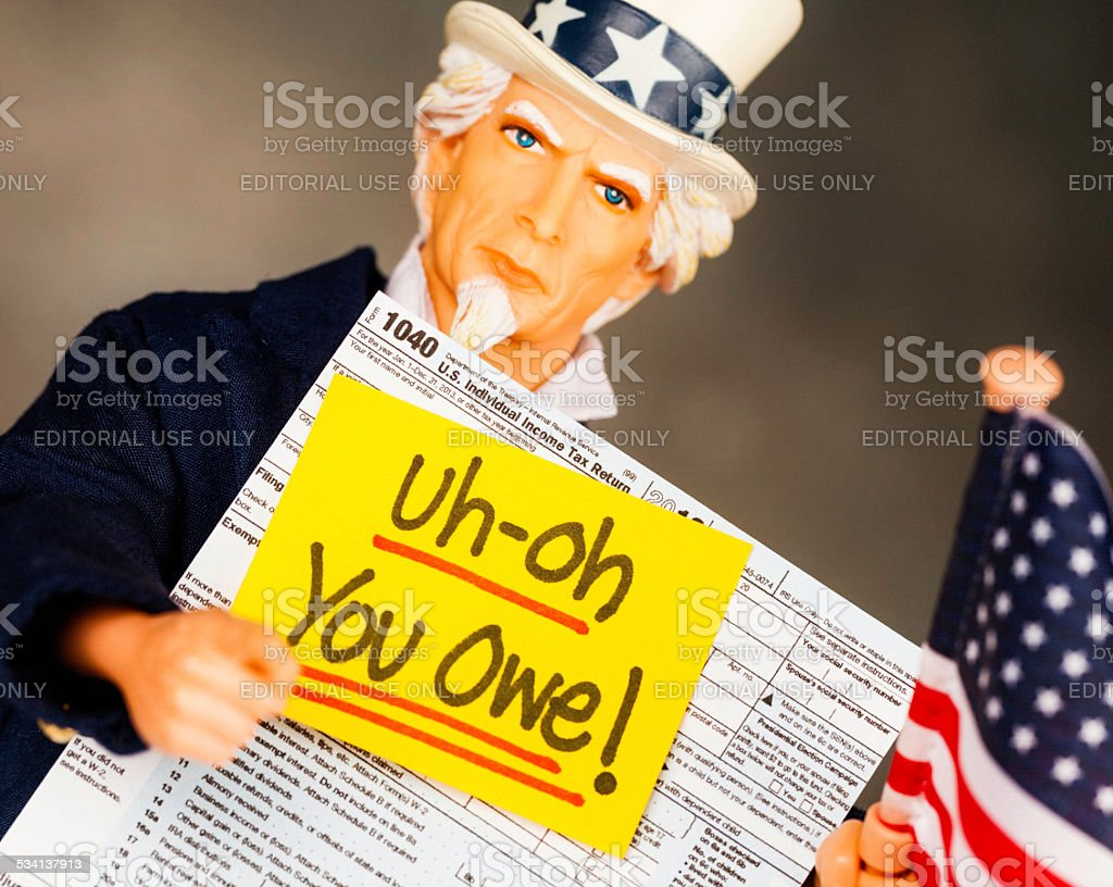 Tax Season: You Owe. Uncle Sam with US Form 1040 stock photo