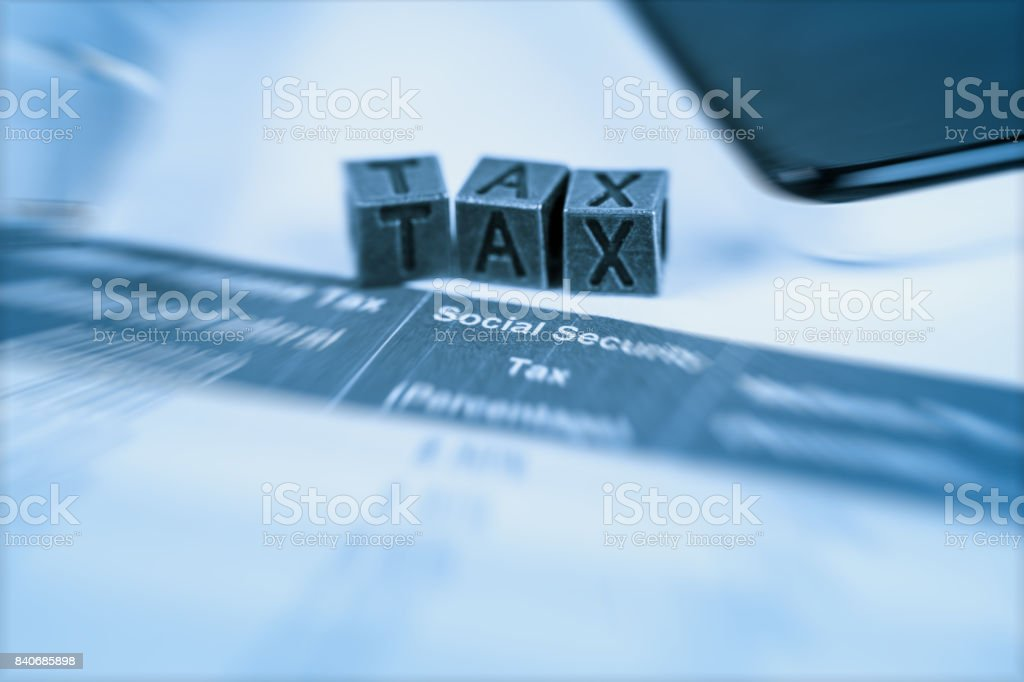 Tax spreadsheet with copper tax cubic in radial blur stock photo