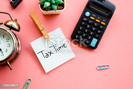tax time concept on sticky note, calculator and clock on pink background