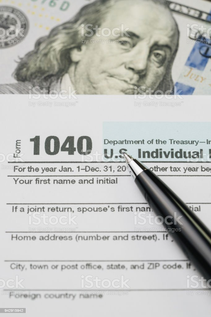 Tax time concept, pen on 1040 US individual income tax filling form...
