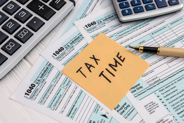 'Tax time' memo on 1040 individual tax form 'Tax time' memo on 1040 individual tax form taxes stock pictures, royalty-free photos & images