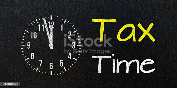 tax time, message on blackboard with clock