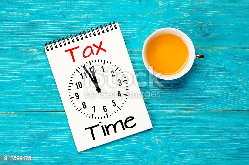 tax time, message with clock in notepad over turquoise office table
