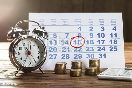 istock Tax Time On Alarm Clock With Coins 921353736