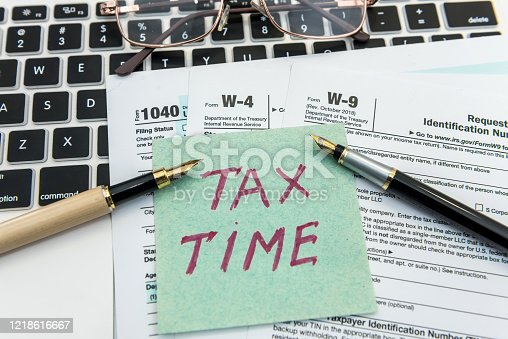 184625018 istock photo Tax time on sticker wit calculator on tax form 1218616667