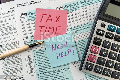 184625018 istock photo Tax time on sticker wit calculator on tax form 1241749023