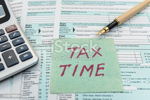 184625018 istock photo Tax time on sticker wit calculator on tax form 1249798804