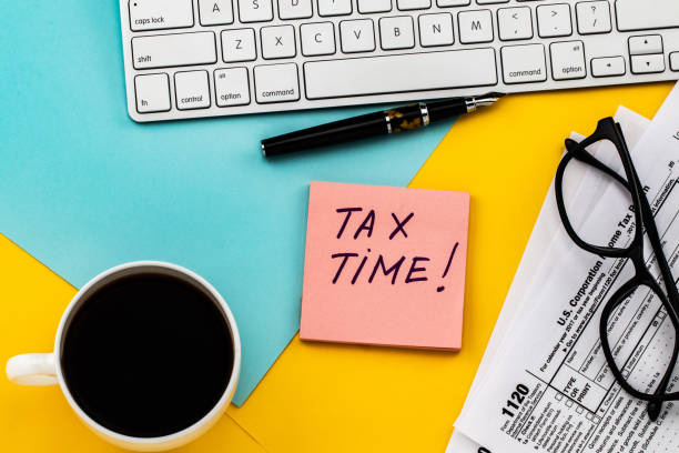 Tax Time  written on  paper note with tax form, and cup of coffee Tax Time  written on  paper note with tax form, and cup of coffee. taxes stock pictures, royalty-free photos & images