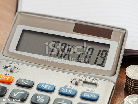 istock Tax word and 2019 number on calculator. Business and tax concept. Pay tax in 2019 years. 1075926824