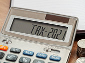 istock Tax word and 2021 number on calculator. Business and tax concept. Pay tax in 2021 years. 1276983199