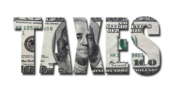 Taxes text cutout from hundred dollar bil stock photo