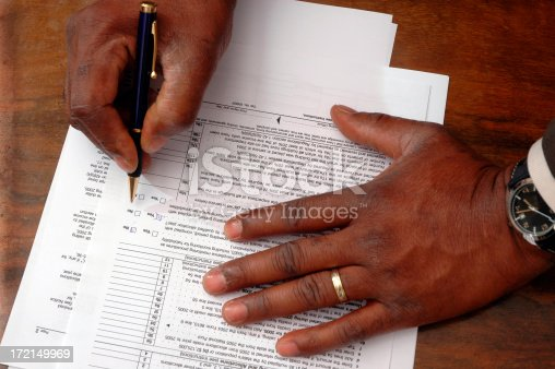 Blck man hands filling taxes forms.