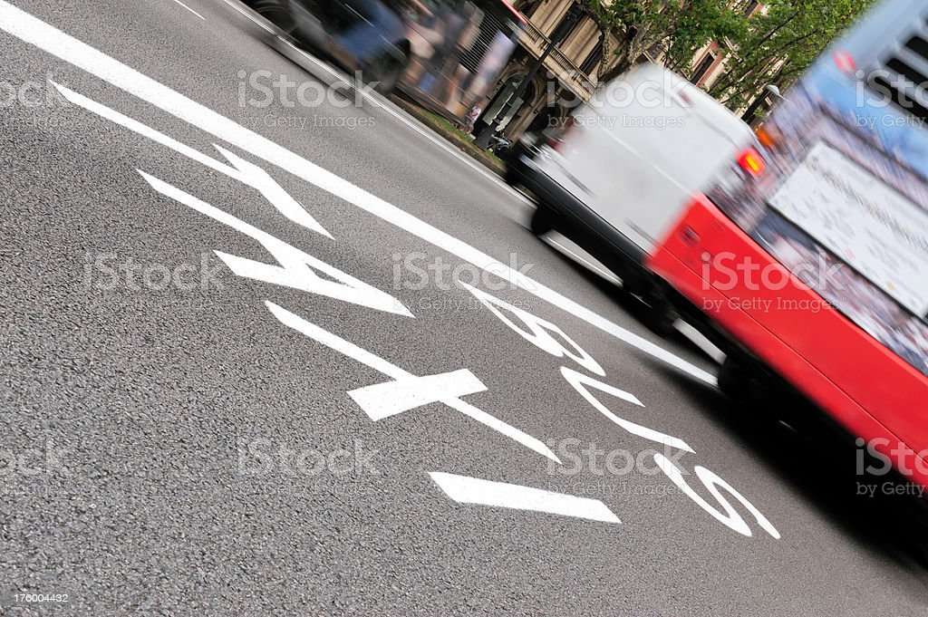 Taxi and bus lane Motion blurred bus and other traffic moving away. Bus and taxi lane painted on asphalt. Motion blurred daytime traffic Asphalt Stock Photo