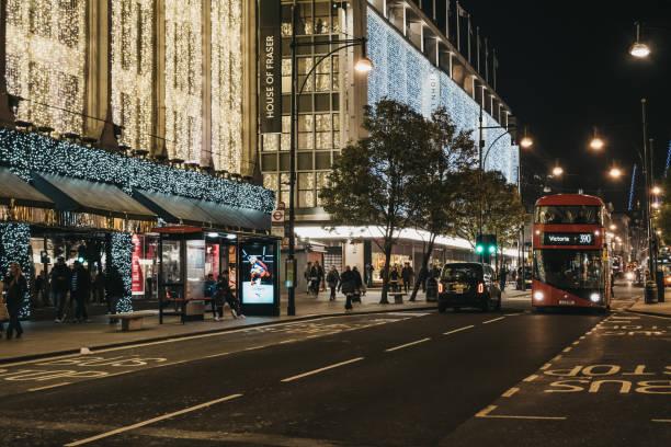 在英國倫敦牛津街的計程車和巴士,從弗雷澤之家和約翰路易斯購物中心裝飾聖誕燈。 - john lewis 個照片及圖片檔
