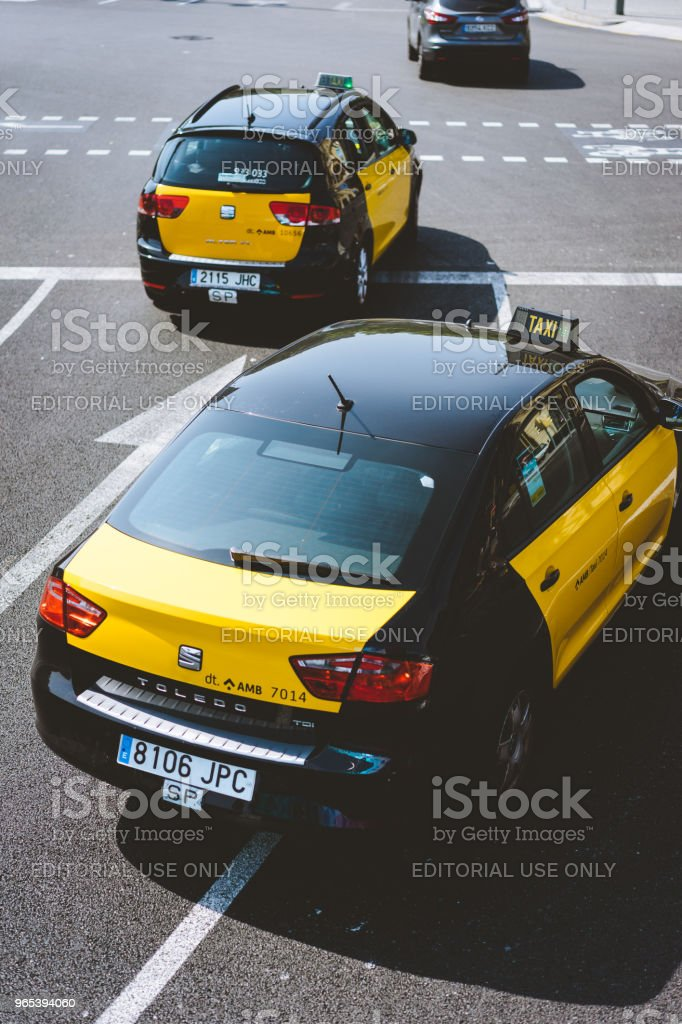 Taxi at the road junction of the city of Barcelona in Spain. Classic taxi yellow and black. Hybrid car zbiór zdjęć royalty-free
