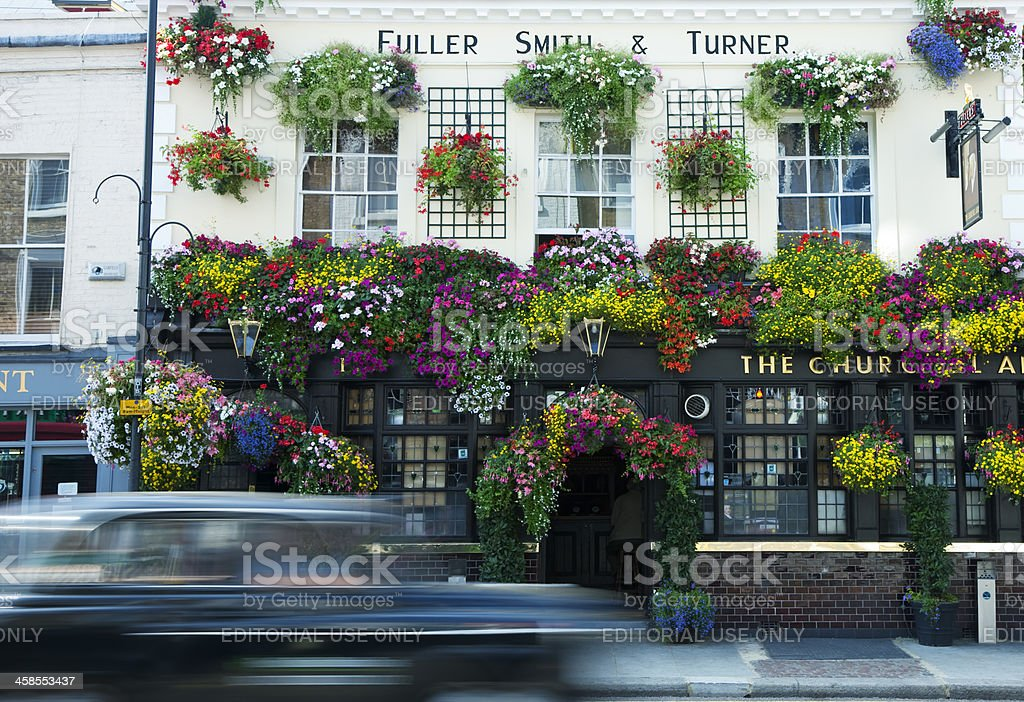 Taxi Cab Driving Past Traditional London Pub Decorated with Flowers stock photo