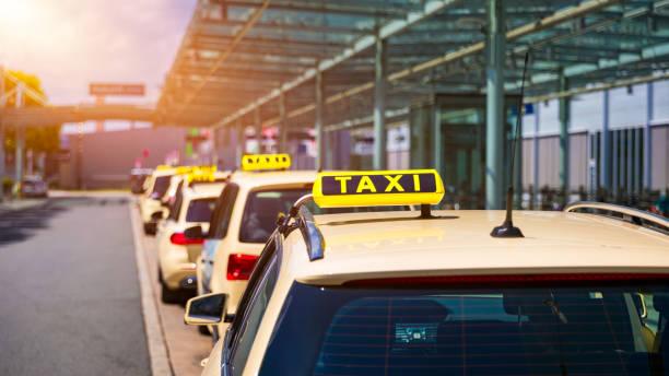 Taxi-Kabinen warten auf Fahrgäste. Gelbes Taxi-Schild auf Fahrerkabinen. Taxiwagen warten auf die Ankunftsgäste vor dem Airport-Gate. Taxis stehen am Terminal des Flughafens und warten auf Passagiere. – Foto