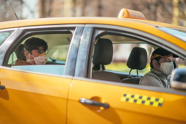Taxifahrer und sein Beifahrer tragen Schutzmasken während der Luftverschmutzung oder Krankheitsepidemie – Foto