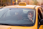 istock Taxi driver and his passenger are wearing protective masks during air pollution or illness epidemic 1224376033