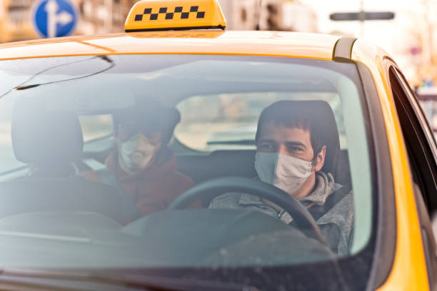 Taxi driver and his passenger are wearing protective masks during air pollution or illness epidemic