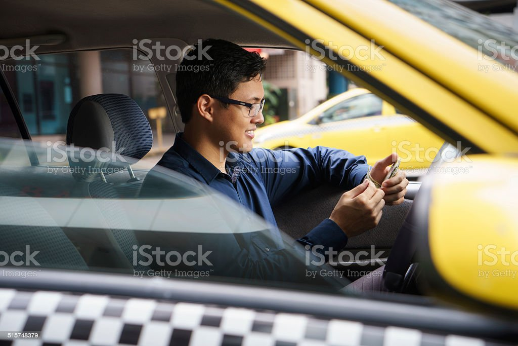 taxi driver driving car happy counting money stock photo