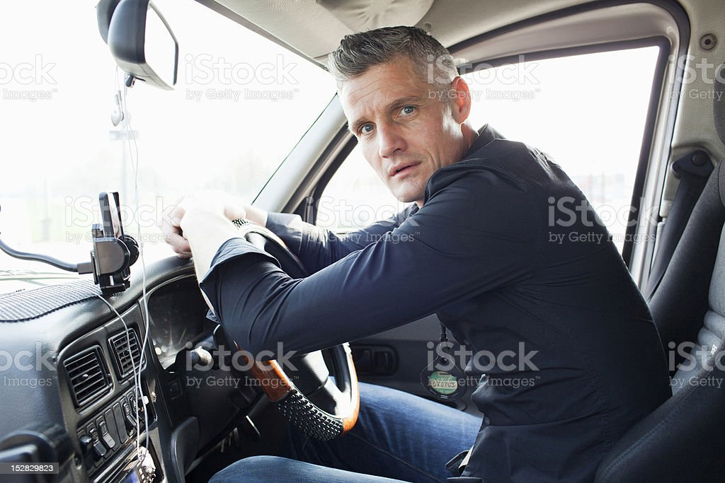Taxi driver sitting at steering wheel stock photo