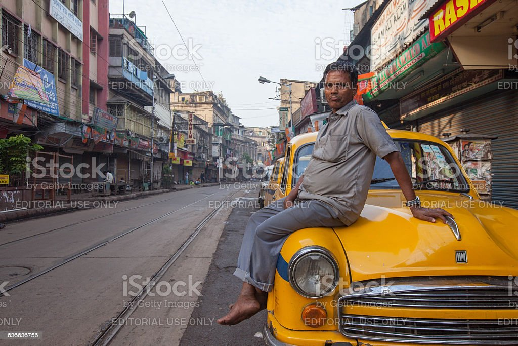 Taxi driver sitting on a yellow Ambassador in Kolkata, India stock photo