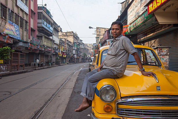 Taxi driver sitting on a yellow Ambassador in Kolkata, India stock photo