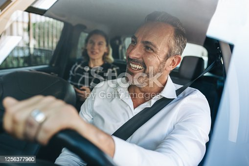 istock Taxi driver talking to a female passenger in car 1256377960