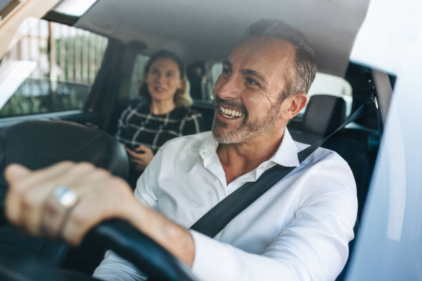 Taxi driver talking to a female passenger in car stock photo